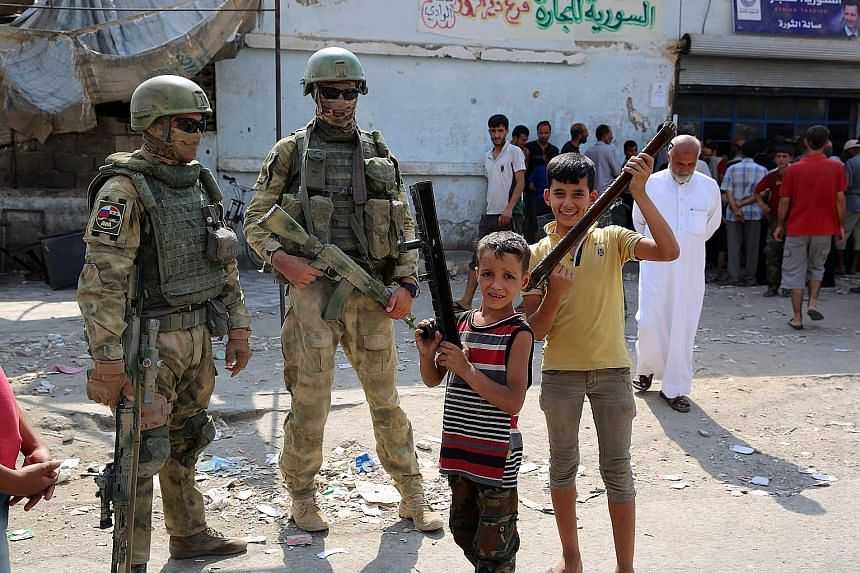 Russian soldiers in the eastern Syrian city of Deir al-Zor. Washington and Moscow support separate offensives in the Syrian conflict, with both advancing against Islamic State in Iraq and Syria militants in the eastern part of Syria.