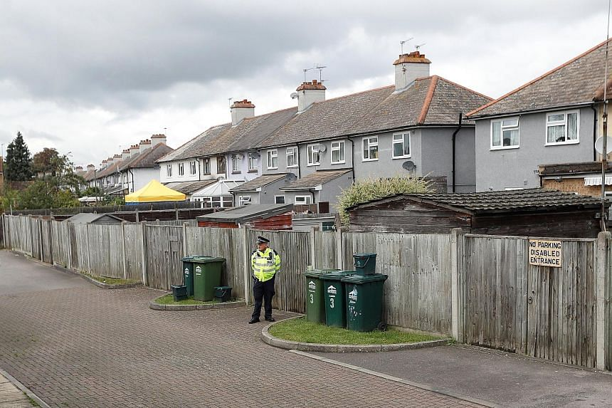 A police officer on guard at the back of a property being searched in the town of Sunbury-on-Thames in Surrey yesterday. The police said the raid was in connection with the arrest of the second suspect in Friday's train bombing.