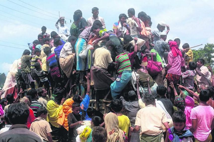 Rohingya refugees climb a truck to receive aid distributed by local organisations at Balukhali makeshift refugee camp in Cox's Bazar, Bangladesh, on Sept 14, 2017.