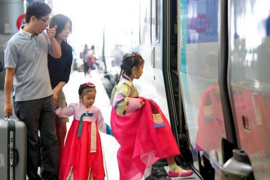 South Korean girls wearing traditional costumes board a train with their parents at a railway station in Seoul ahead of the Chuseok holiday.