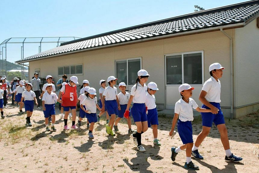 Elementary school students take part in an evacuation drill for a simulated North Korean missile attack, in Abu, Yamaguchi prefecture, Japan, on June 4, 2017.