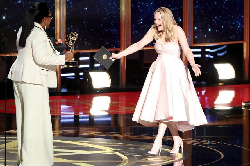 Elisabeth Moss reacts as Oprah Winfrey (left) presents The Handmaid's Tale with the award for Outstanding Drama Series.