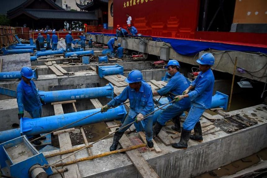Chinese construction personnel work to relocate the main hall of the 135-year old Yufo Temple, also known as the Jade Buddha Temple, in Shanghai on Sept 5, 2017.