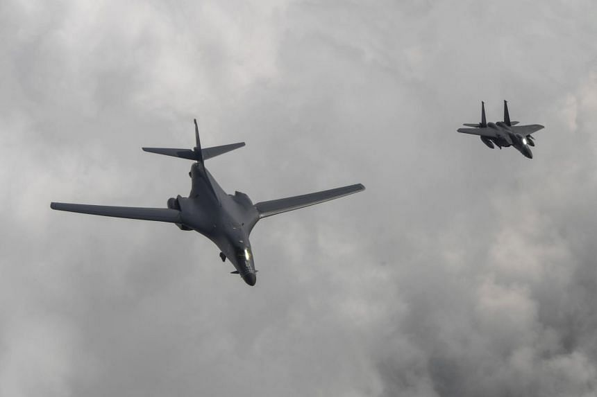 A US B1-B bomber (left) escorted by a South Korean F-15K fighter as they fly over South Korea during a 10-hour mission on July 30, 2017.