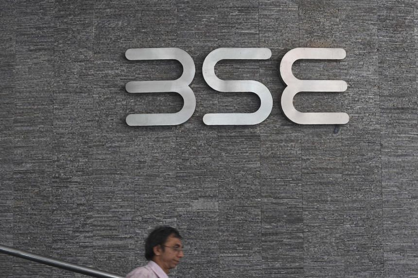 An office worker walks past the Bombay Stock Exchange (BSE) logo at the BSE building in Mumbai, on July 25, 2017.