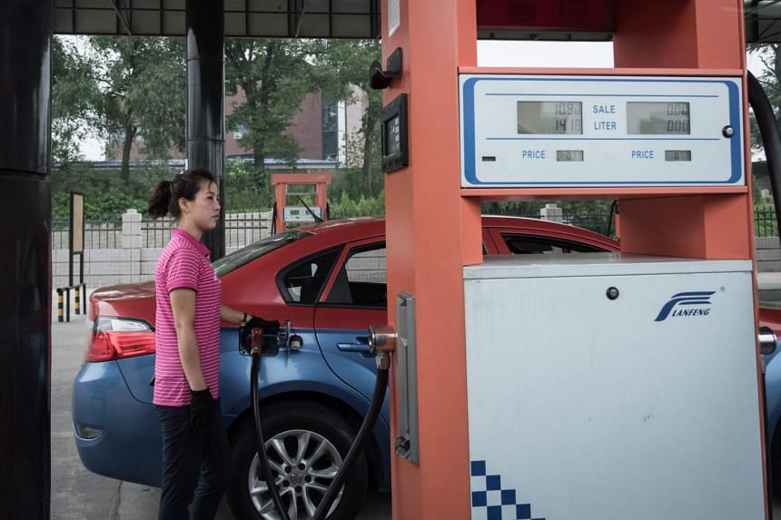 A petrol pump attendant fills up a taxi with gasoline at a fuel station in Pyongyang, on July 21, 2017.