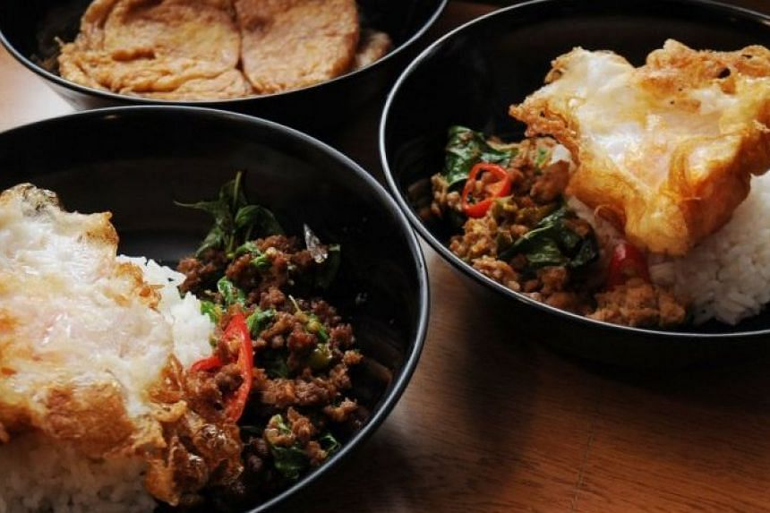 Stir-fried pork or beef with holy basil leaves and rice peek out from under a fried egg or omelette.