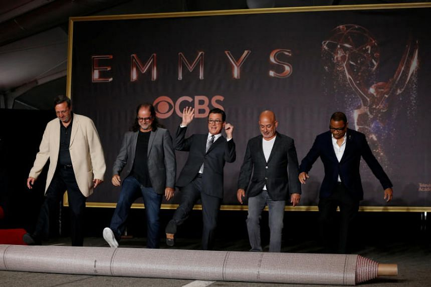 Show host Stephen Colbert (centre) helps roll out the red carpet during preparations for the 69th Emmy Awards in Los Angeles.