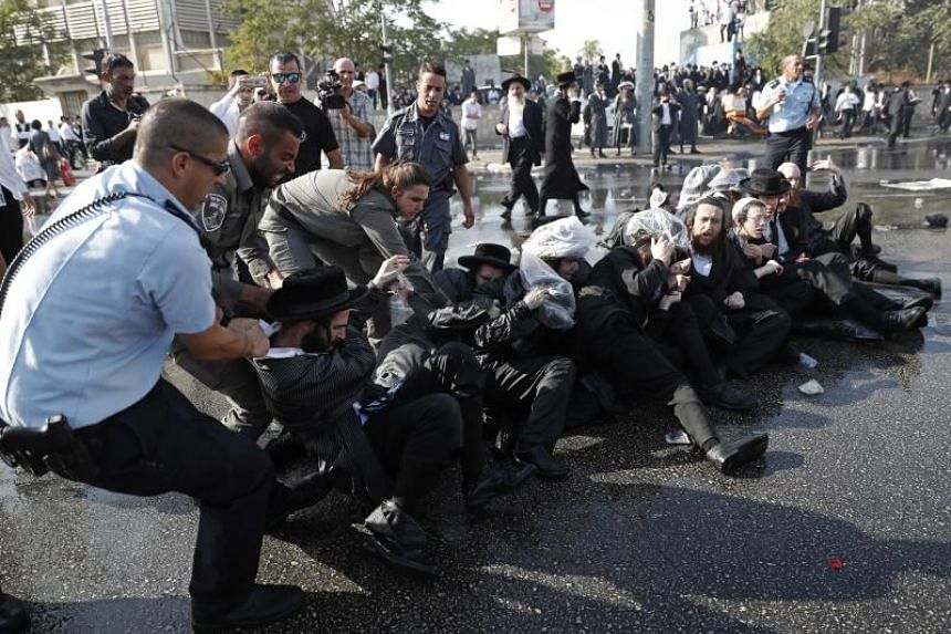 Israeli security forces remove ultra-Orthodox Jewish demonstrators in an ultra-Orthodox neighbourhood of Jerusalem on Sept 17, 2017.