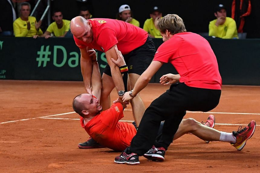 Belgium's Steve Darcis (bottom) celebrates with team captain Johan Van Herck and player David Goffin (right) after defeating Australia's Jordan Thompson in their singles match of the Davis Cup World Group semi final tie between Belgium and Australia,