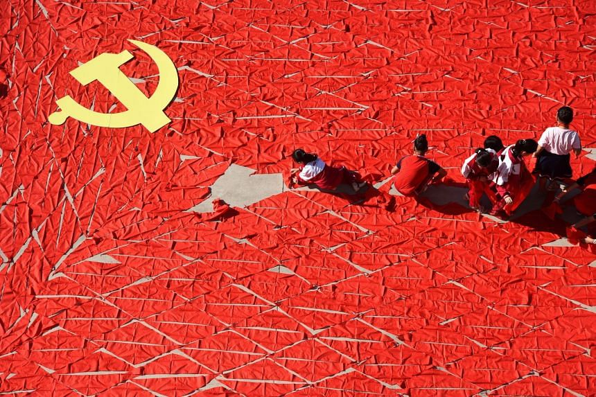 Students use red scarves to make a flag of the Communist Party of China, ahead of the 19th National Congress of the Communist Party, at a primary school in Linyi, Shandong province, China.