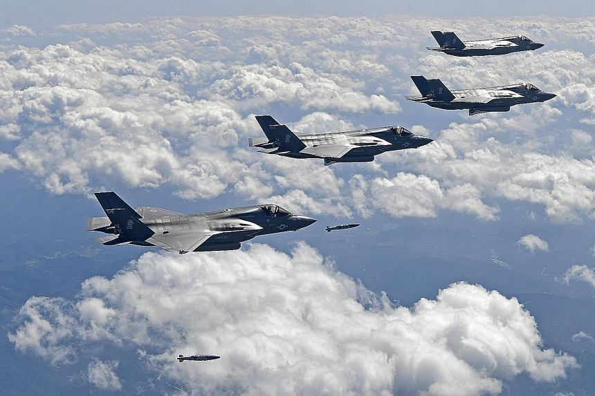 US F-35 jets droppingbombs to hit simulated targets during a drill in South Korea yesterday. According to South Korean Defence Minister Song Young Moo, the joint drills are being held two to three times a month these days.