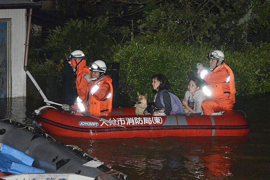 Residents being evacuated by boat from an inundated house in Oita, southern Japan, as Typhoon Talim triggered heavy rain on Sunday.