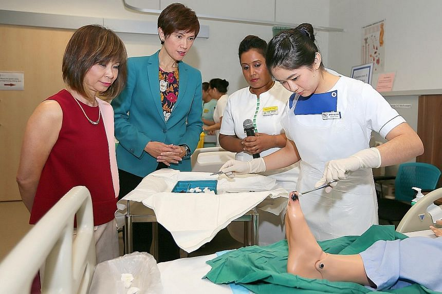 Senior Minister of State for Health Amy Khor and Second Minister for Manpower Josephine Teo observing a wound-dressing procedure by Nanyang Polytechnic nursing student Chan Hui Xin at the SGH Inpatient Simulation Ward.