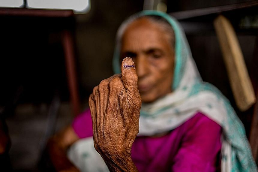 A Nepali woman showing her inked thumb after casting her ballot in the local elections at a polling station in Birgunj Parsa district, south of Kathmandu, yesterday.