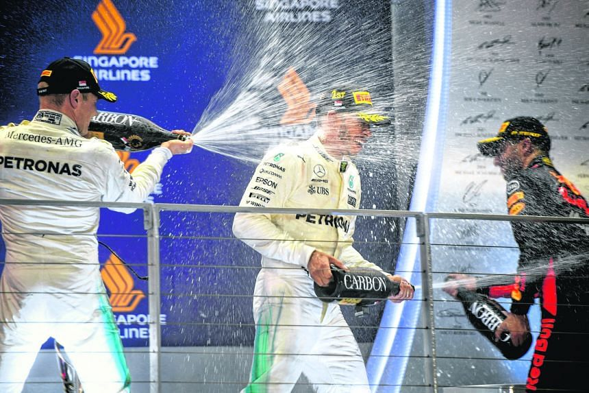 Singapore Grand Prix winner Lewis Hamilton on the podium with second-placed team-mate Valtteri Bottas and Red Bull's Daniel Ricciardo. The Briton leads the world championship by 28 points with six races remaining.