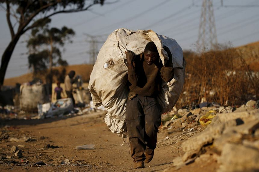 An man carries a bag full of recyclable waste material which he sells for a living, in Daveland near Soweto, South Africa, on Aug 4, 2015.