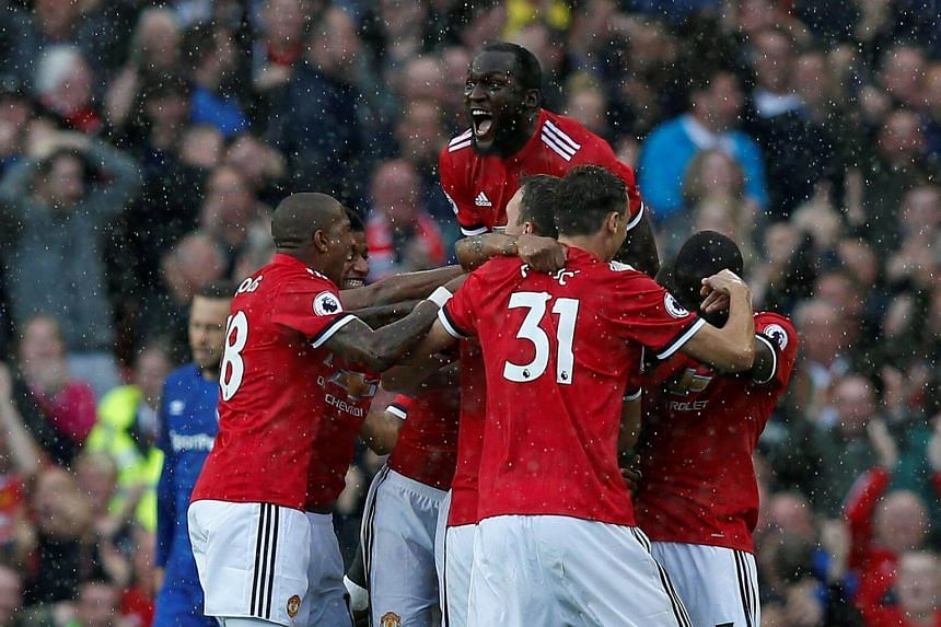 Manchester United's Antonio Valencia celebrates scoring their first goal with team mates and Romelu Lukaku, on Sept 17, 2017.