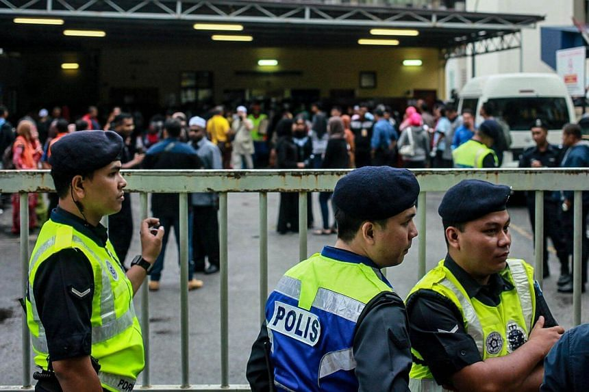 Malaysian police officers manning the gate of a hospital as relatives gather inside the forensics wing, on Sept 14, 2017.
