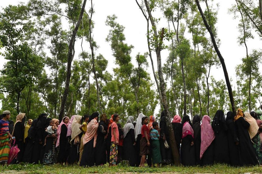 Rohingya refugees wait in line for relief supplies in the refugee camp of Leda near Teknaf on Sept 19, 2017.