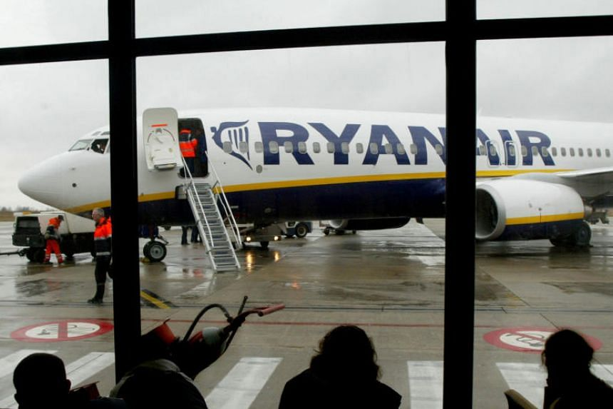 Travellers wait in front of a passenger jet belonging to Irish discount airline Ryanair at Charleroi airport.