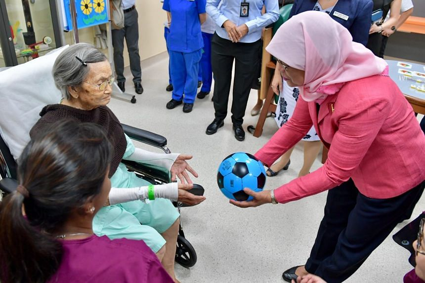 President Halimah Yacob watching 100-year old Mdm Liew Tim undergoing a therapy session at the National University Hospital on Sept 19, 2017.