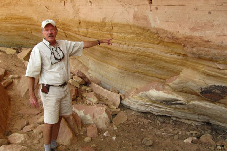 Dreamland Safari guide Jeff Frey points to rock art on the cliffside at Long Canyon in the Grand Staircase-Escalante National Monument in Kanab, Utah,