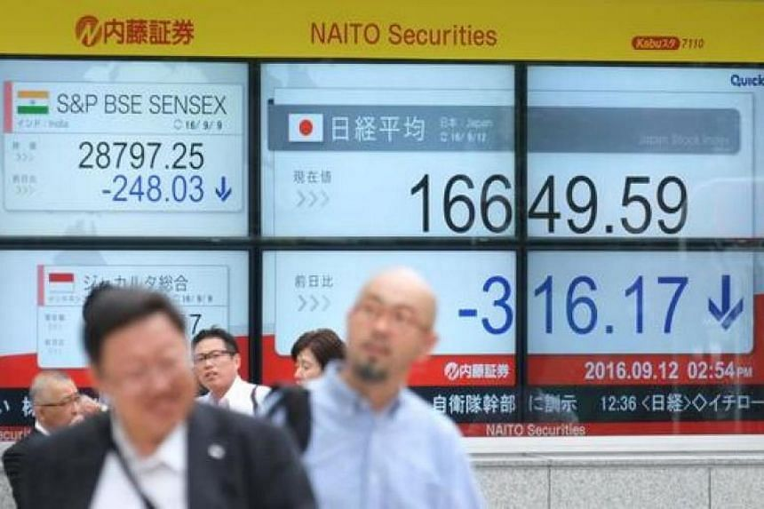 Pedestrians walk past an electric quotation board displaying the Nikkei key index of the Tokyo Stock Exchange in Tokyo on Sept 12, 2016.