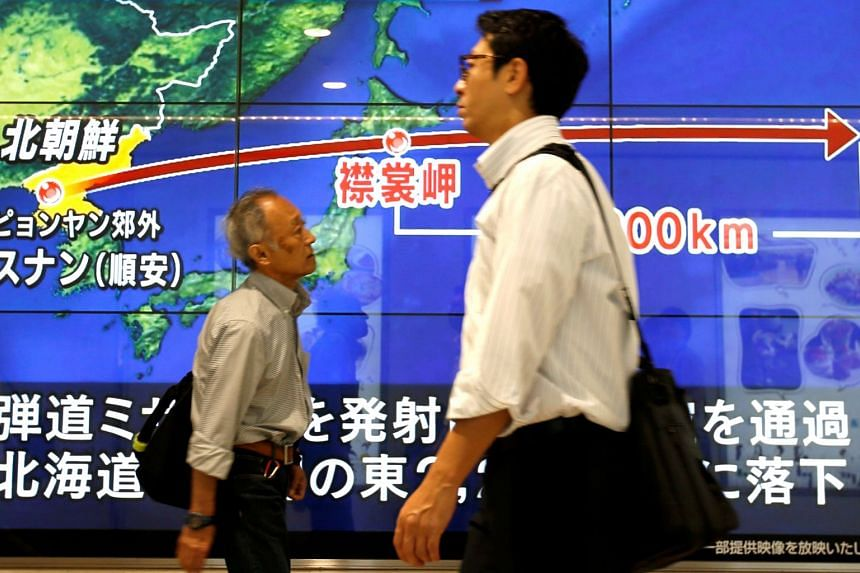 Passersby walk in front of a TV screen reporting news about North Korea's missile launch, in Tokyo.
