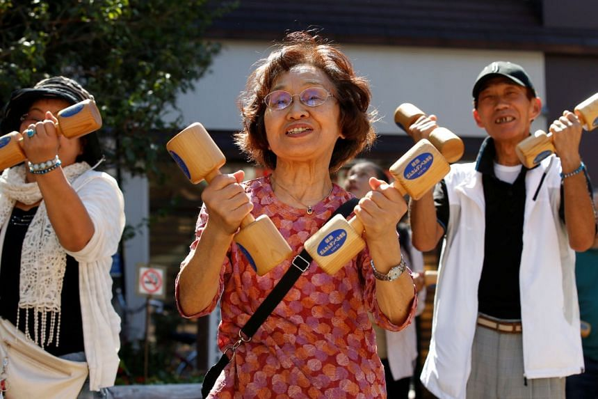 Elderly and middle-aged people exercise with wooden dumbbells during a health promotion event to mark Japan's Respect for the Aged Day at a temple in Tokyo's Sugamo district, on Sept 18, 2017.