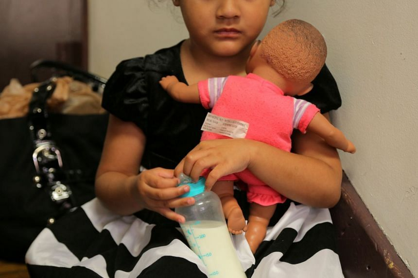A girl from El Salvador hugs her doll.
