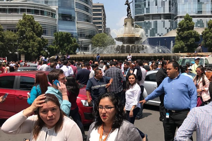 People react after an earthquake hit in Mexico City.