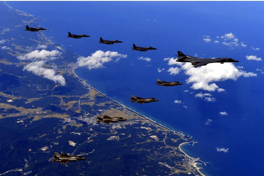 South Korean F-15K combat planes (top left), a US Air Force B-1B bomber plane (centre right) and F-35B combat planes (bottom left) flying in the sky over South Korea while being on a bombing drill mission to hit simulated targets.