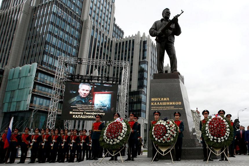 Guards of honour stand next to a monument to Mikhail Kalashnikov, the Russian designer of the AK-47 assault rifle, during its opening ceremony in Moscow, Russia on Sept 19, 2017.