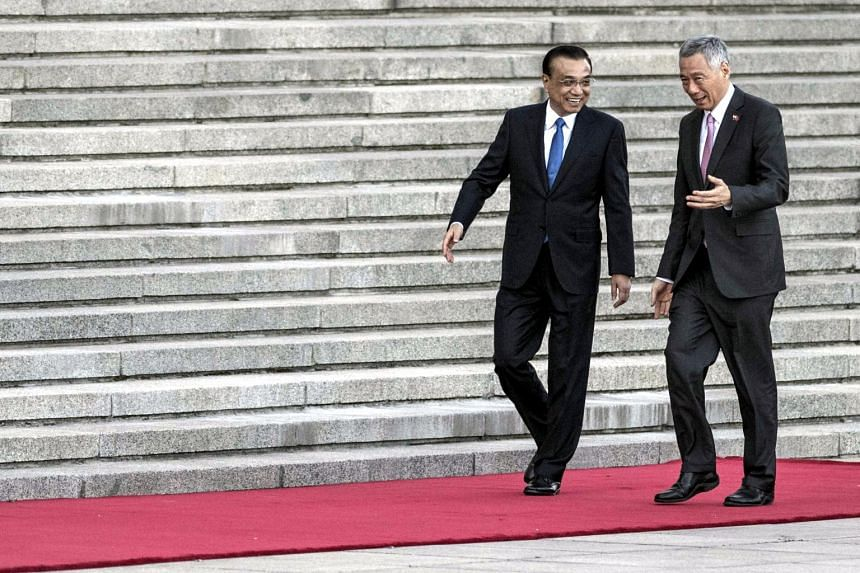 Chinese Premier Li Keqiang (left) speaks with PM Lee Hsien Loong during a welcome ceremony at the Great Hall of the People in Beijing, on Sept 19, 2017.