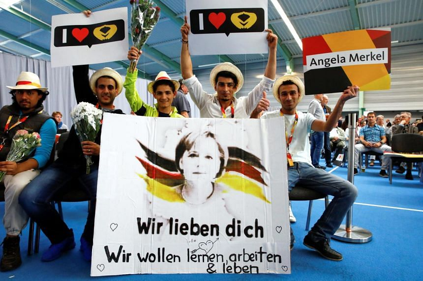 """Supporters of German Chancellor Angela Merkel, a top candidate of the Christian Democratic Union Party (CDU) for the upcoming general election, holding posters reading """"We love you""""."""