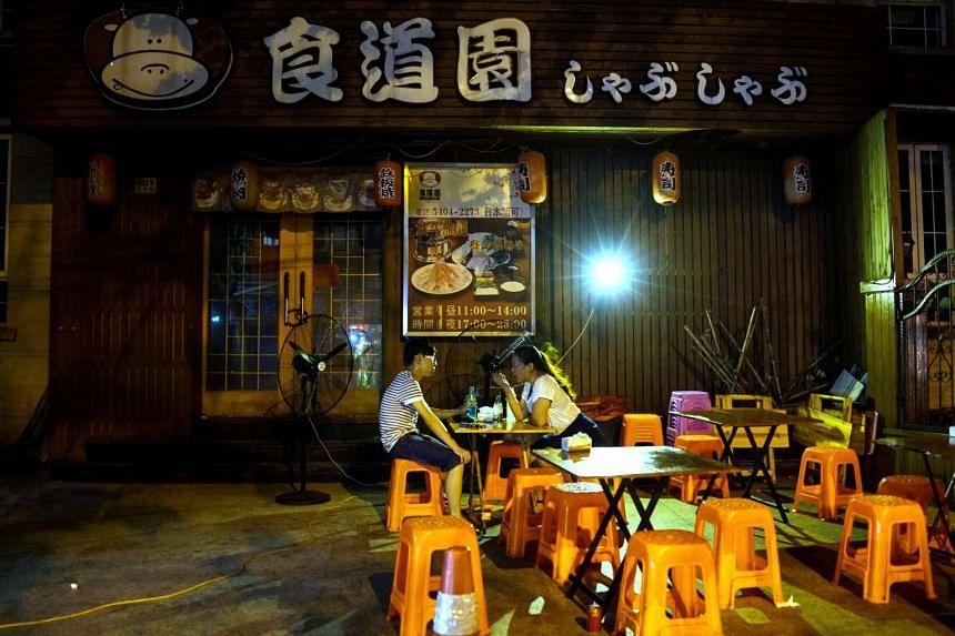 A couple talk having dinner at a roadside restaurant in Shanghai, on July 29, 2017.