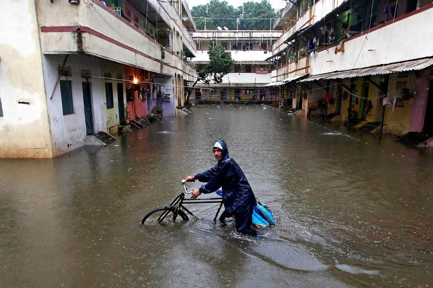 A delivery boy pushes his bicycle through a water-logged street after heavy rains at a residential colony in Mumbai on Sept 20, 2017.