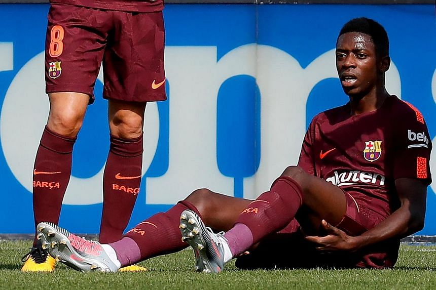 Barcelona's record signing Ousmane Dembele reacts after suffering a hamstring injury during the LaLiga match against Getafe.