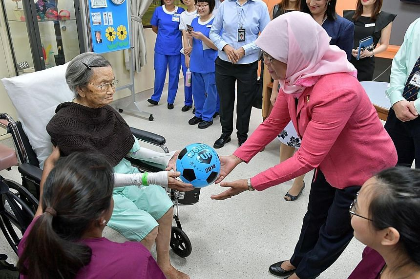 """President Halimah Yacob interacting with 100-year-old Madam Liew Tim in the ward after her therapy session at NUH yesterday. Madam Halimah said she hoped her visit would demonstrate her support for healthcare workers, adding that they have """"done very"""