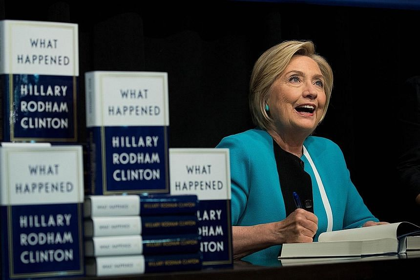 Former US presidential candidate Hillary Clinton signing copies of her new book, What Happened, on Sept 12 in New York City. The book details her campaign and election loss last year.