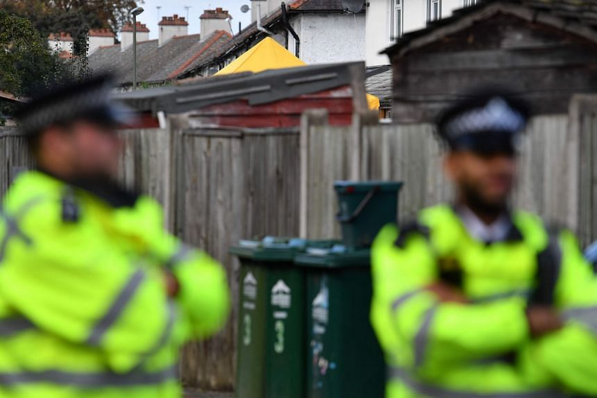 Police stand guard at a house in Sunbury, west of London, Sept 18, 2017, as investigations continue.