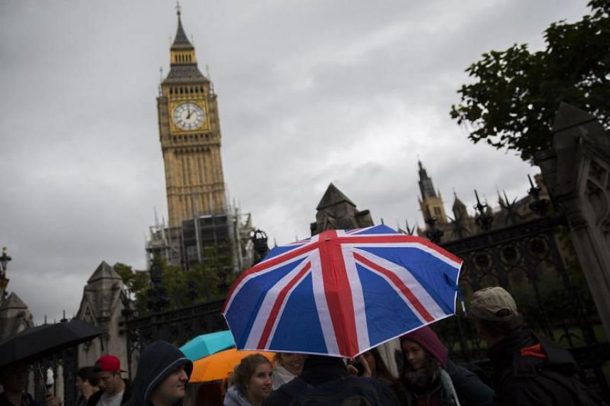 A tourist carrying a Union Jack-coloured umbrella as he passes the Houses of Parliament in London.