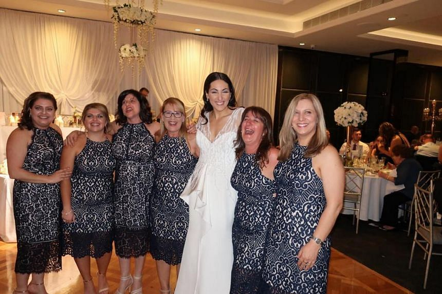 The bemused bride, Julia Mammone, posing for a photo with her six guests who wore the same dress to her wedding.