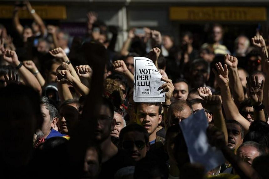 """A man holds a placard reading """"We vote to be free"""" during a protest near the Economy headquarters of Catalonia's regional government in Barcelona on Sept 20, 2017."""