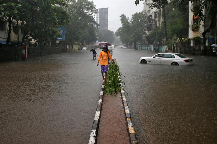 A girl walks on a road divider in a water-logged street as it rains in Mumbai, India, Sept 20, 2017.