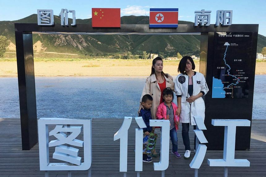 Tourists pose at the border with North Korea in Tumen, China, on Aug 30, 2017.