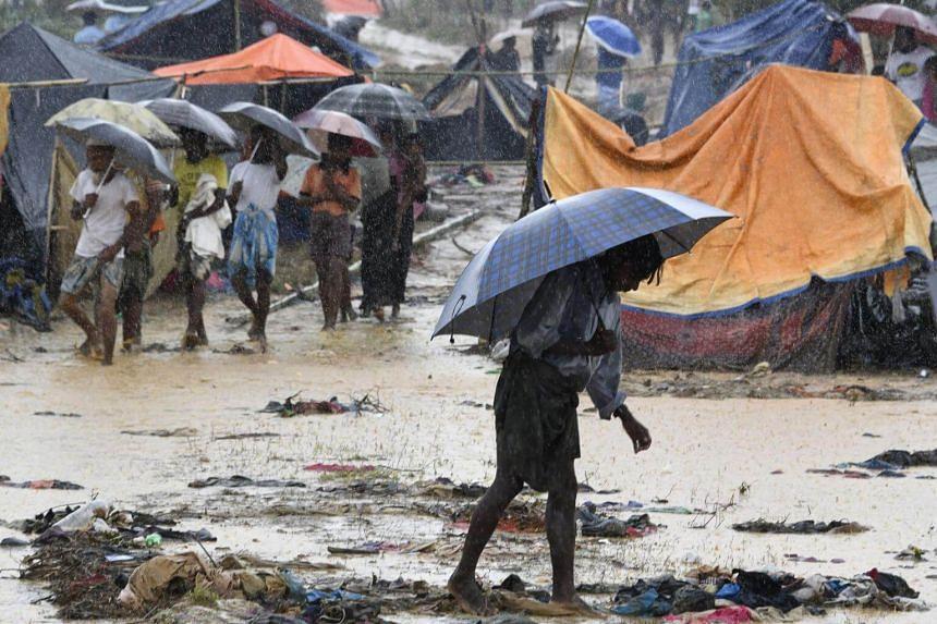 A Rohingya refugee holds an umbrella during rain in Bangladesh's Balukhali refugee camp on Sept 17, 2017.