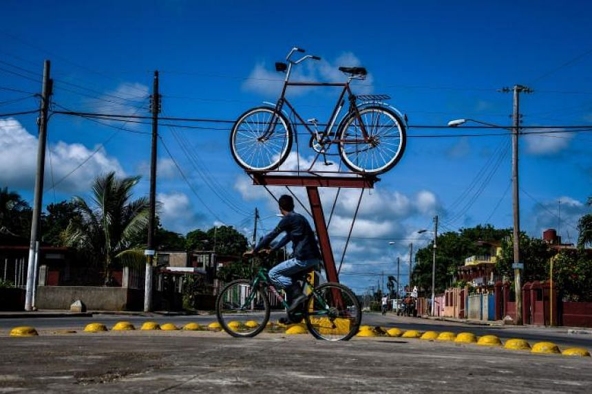 A Cuban rides his bike past a bicycle monument in Cardenas, a city 130km east of Havana, on August 30, 2017.