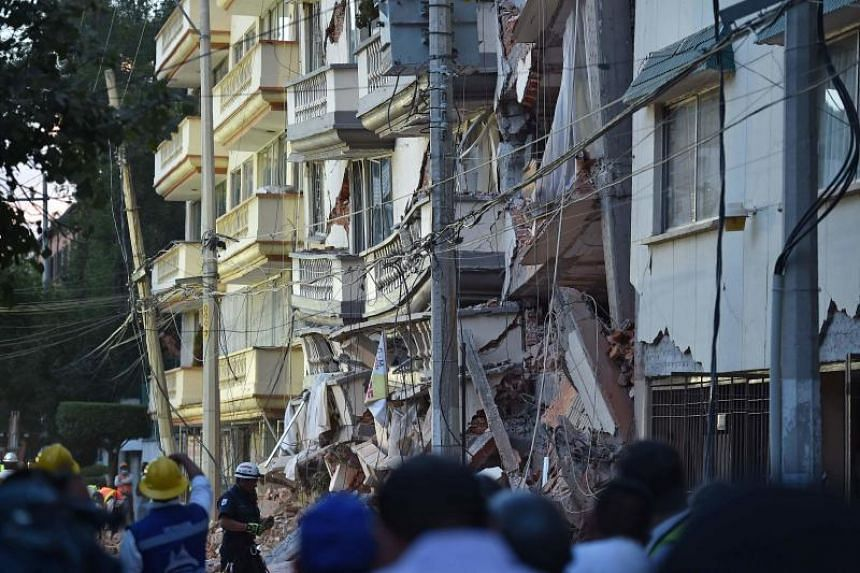 Rescuers, firefighters, policemen, soldiers and volunteers remove rubble and debris from a flattened building in search of survivors after a powerful quake in Mexico City on Sept 19, 2017.